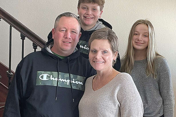 Beth Rull in her Bunker Hill home with her husband, Brandon, their son, Nick, and their daughter, Sophie.