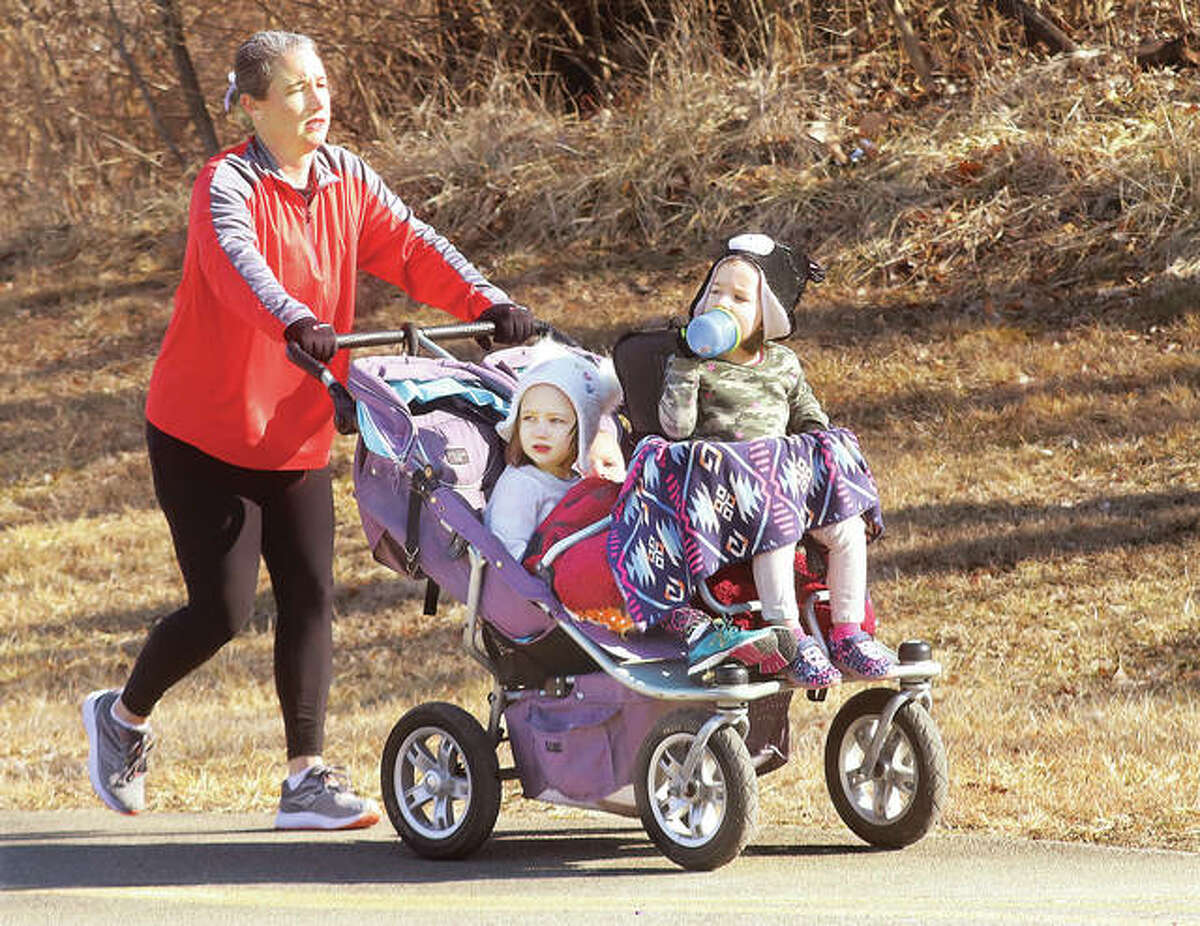 The kids had it easy going Thursday as they went for a stroll with mom near Esic Drive in Edwardsville. Tiffany Suchomski was doing all the work as she pushed her daughters, Magnolia, 5, center, and Martha, 3, right. The Metro East Park and Recreation District is marking its 20th year, with $32.8M invested into 199 park and trail projects.