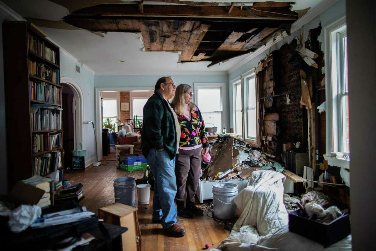 Judie and Martin Beller stand in the middle of their destroyed living room. The couple tried to stay as warm as they could when temperatures dipped into the teens during the Winter Storm Uri by using gas fireplace.