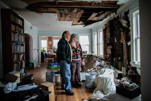 Judie and Martin Beller stand in the middle of their destroyed living room, Thursday, Feb. 25, 2021, in Houston. The couple tried to stay as warm as they could when temperatures dipped into the teens during the Winter Storm Uri. They turned on their gas fireplace, which they hadn't used, and soon their home was taken over by fire.