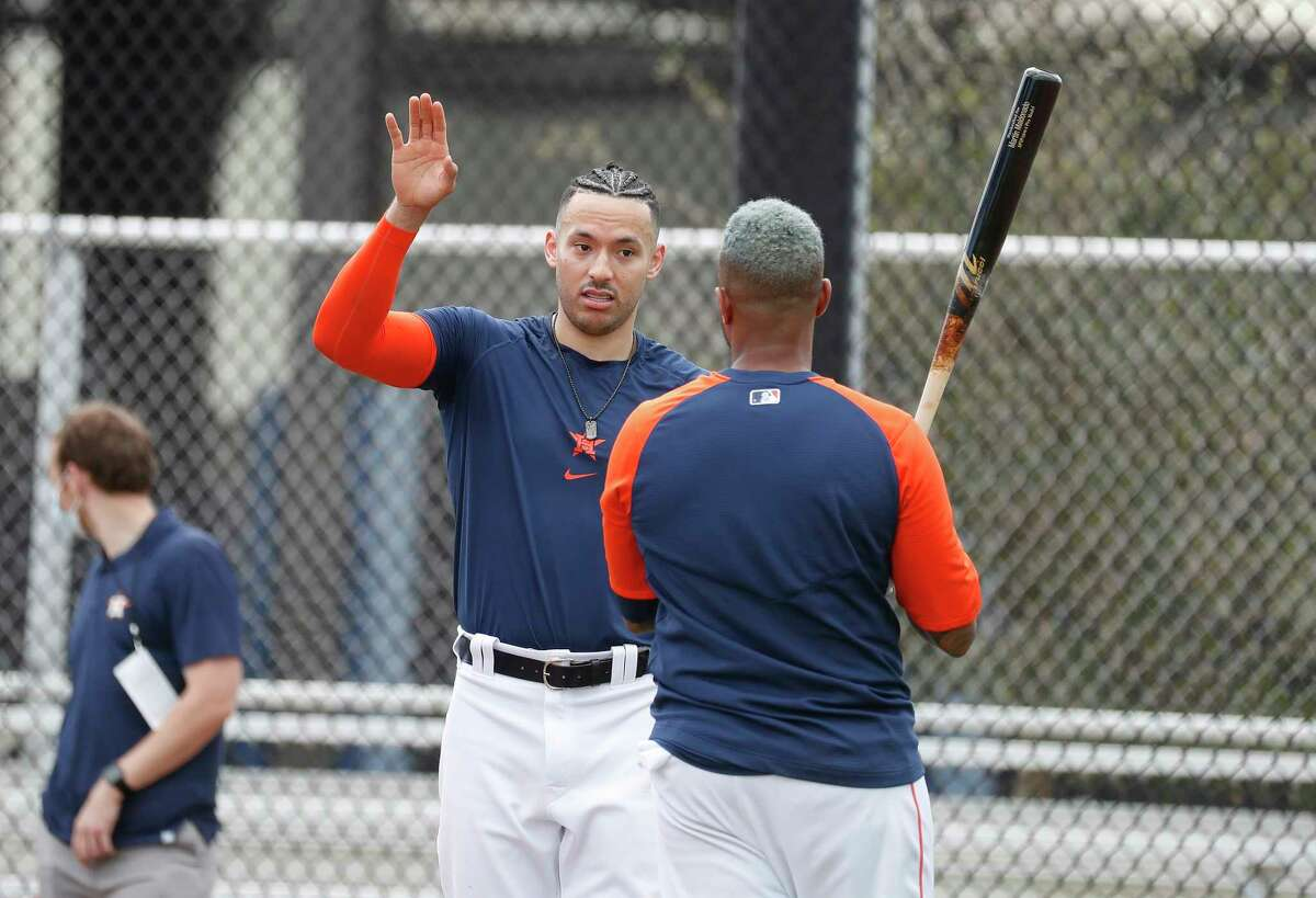Houston Astros shortstop Carlos Correa with his new hairdo talks with catcher Martin Maldonado during spring training workouts for the Astros at Ballpark of the Palm Beaches in West Palm Beach, Florida, Friday, February 26, 2021.
