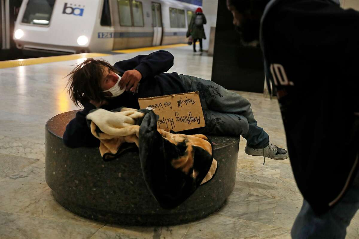 Homeless man Chad Cahill is awoken by a man as Cahill tries to sleep at Civic Center BART station in San Francisco, Calif., on Wednesday, February 25, 2021.