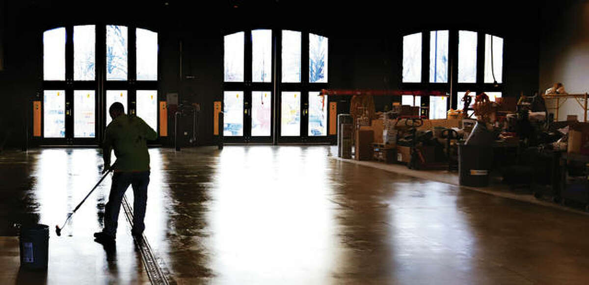 A worker applies another layer of sealer to the floor of the bays that will soon house the village fire department. Interior work is progessing and the building is nearing completion.