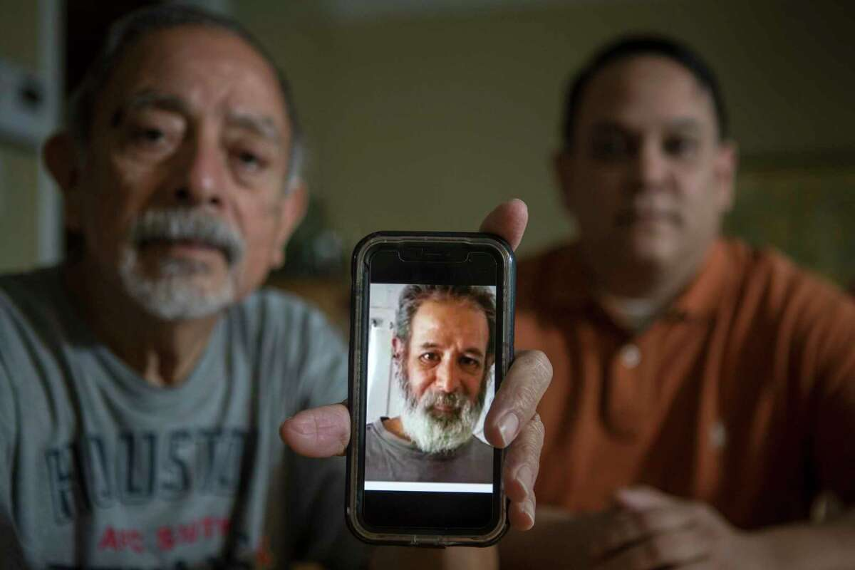 Isaac and Lawrence Ibarra show a picture Isaac's brother, Gilbert Rivera, on a phone Wednesday, Feb. 24, 2021 in Houston. Rivera died of hypothermia after his apartment lost power amid bitter cold temperatures during the week of Feb. 14, 2021.