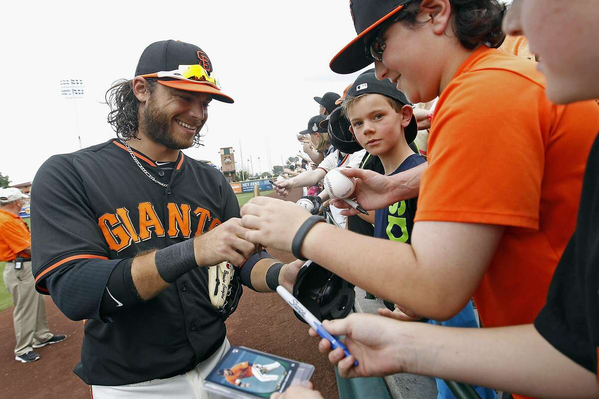 Giants' shortstop Brandon Crawford signs autographs for fans before the start of a 2015 Cactus League game.