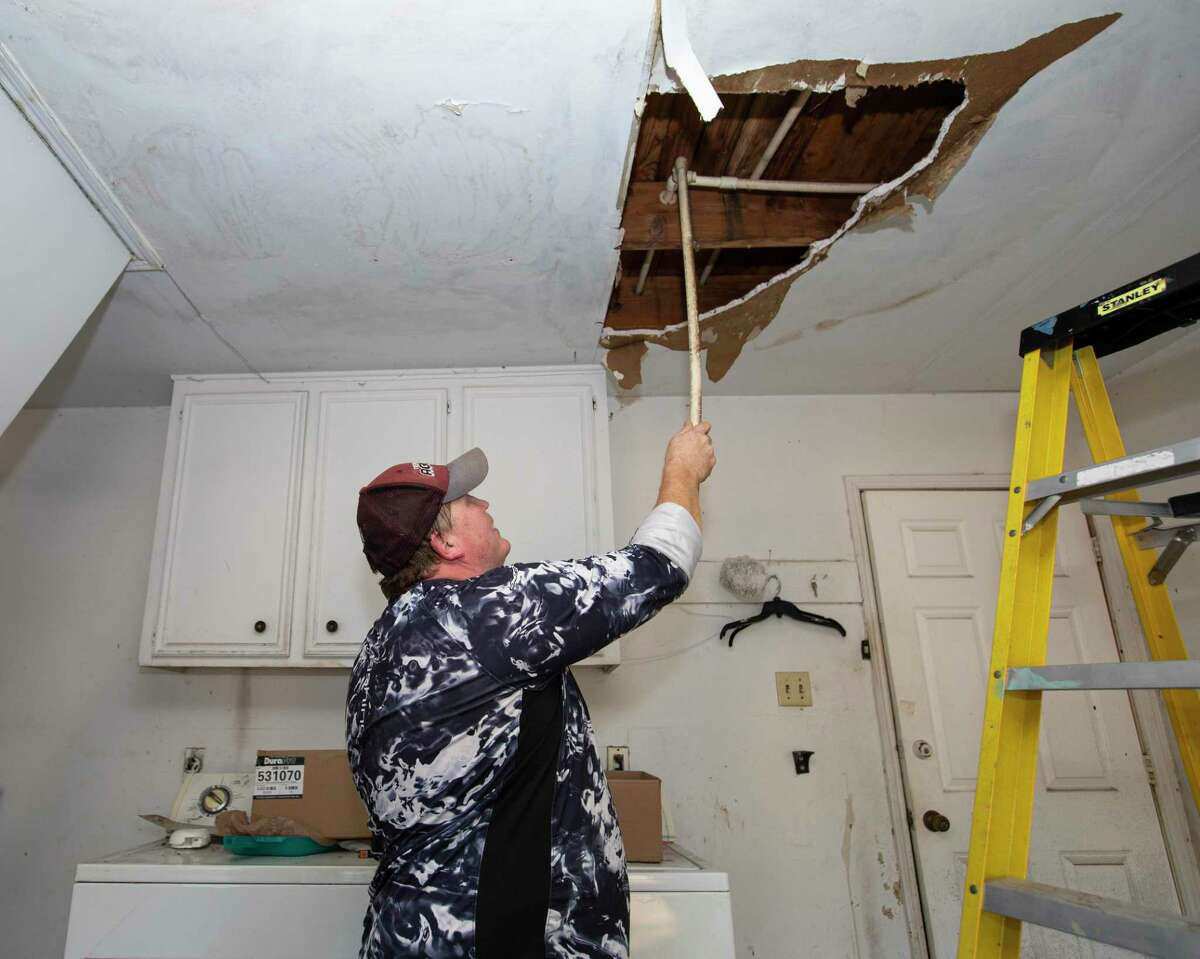 Home owner Thomas Davenport tries to fix the burst pipes at his rental home on Feb. 22, 2021, in northwest Houston. Damage from the freeze has been blamed in part on failure for infrastructure, specifically power reliability, not keeping up.