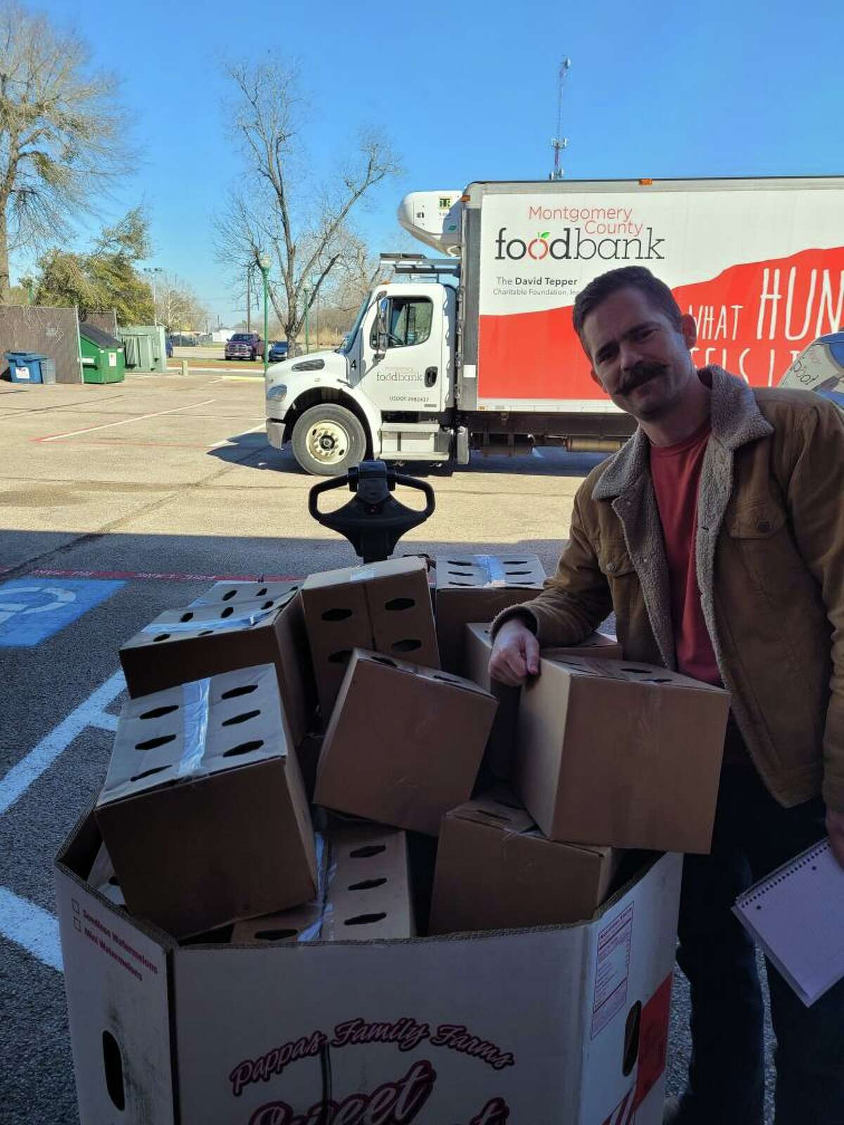 A Montgomery County Food Bank Truck arrives at Honor Cafe on Friday, Feb 19, the first day the restaurant was able to open after the storms, to pick up non perishable food items donated by restaurant patrons, Rotarians, and the restaurant itself. Pictured with the donation is Rotary Club of Conroe member Dustin Bass.