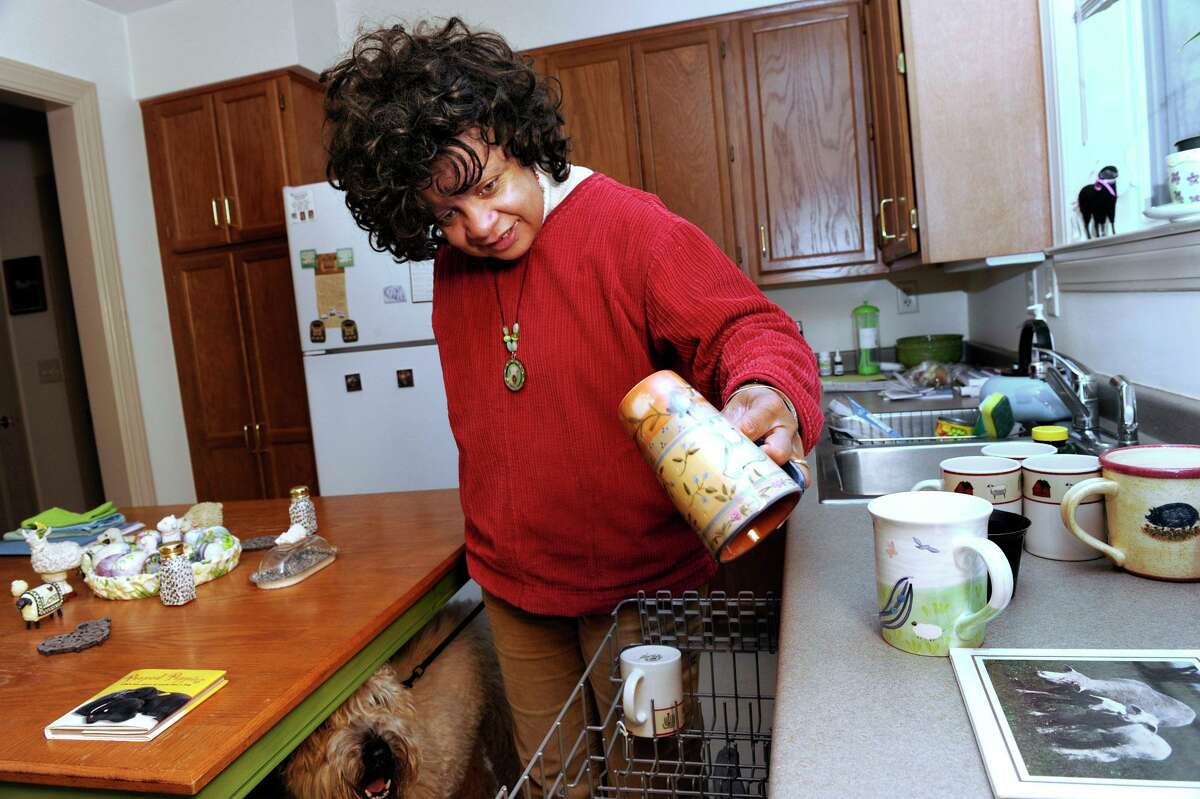 Carolyn Dion empties the dishwasher in her kitchen at Indian Fields, an affordable housing complex in New Milford on Thursday, January 12, 2012.