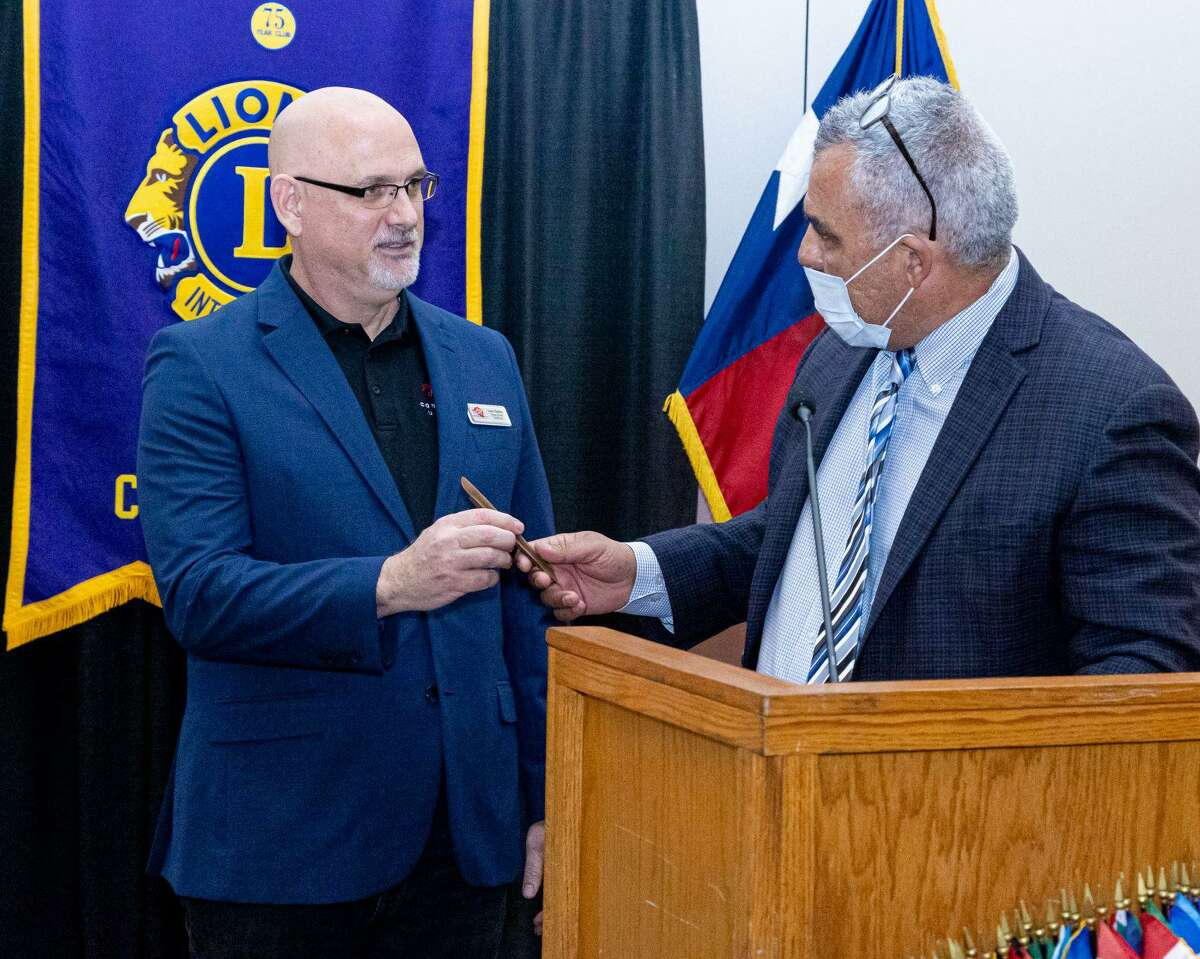 Luke Redus, left, gave a program last week to the Conroe Noon Lions Club about Compassion United and it's Miracle City project to assist the homeless population in our area. Pictured here with Club President Rafael Perez, right, presenting him with a cherished club pen.