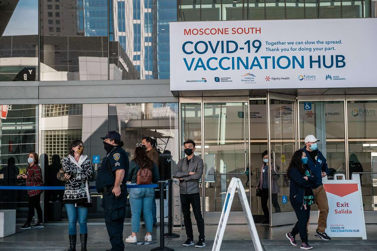 People are seen waiting on line to enter the mass vaccination site at the Moscone Center in San Francisco. The CDC warns of national rise in virus cases, but Bay Area is still dropping and counties are reopening.