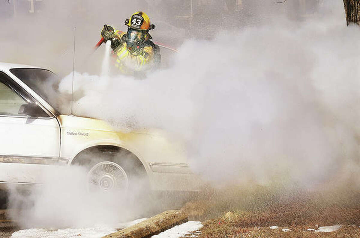 An East Alton firefighter works to extinguish a pesky fire under the hood of an Oldsmobile Cutlass Ciera Monday in front of the East Alton Public Library on Washington Street.