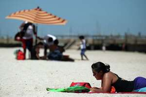 Antonia Moran, of Newscastle, England, soaks up the sun Tuesday, Aug. 13, 2013 as she reads on McGee Beach along the Corpus Christi, Texas, Bayfront. Moran was in town visiting family as temperatures approached the century mark in the Coastal Bend. (AP Photo/Corpus Christi Caller-Times, Michael Zamora)