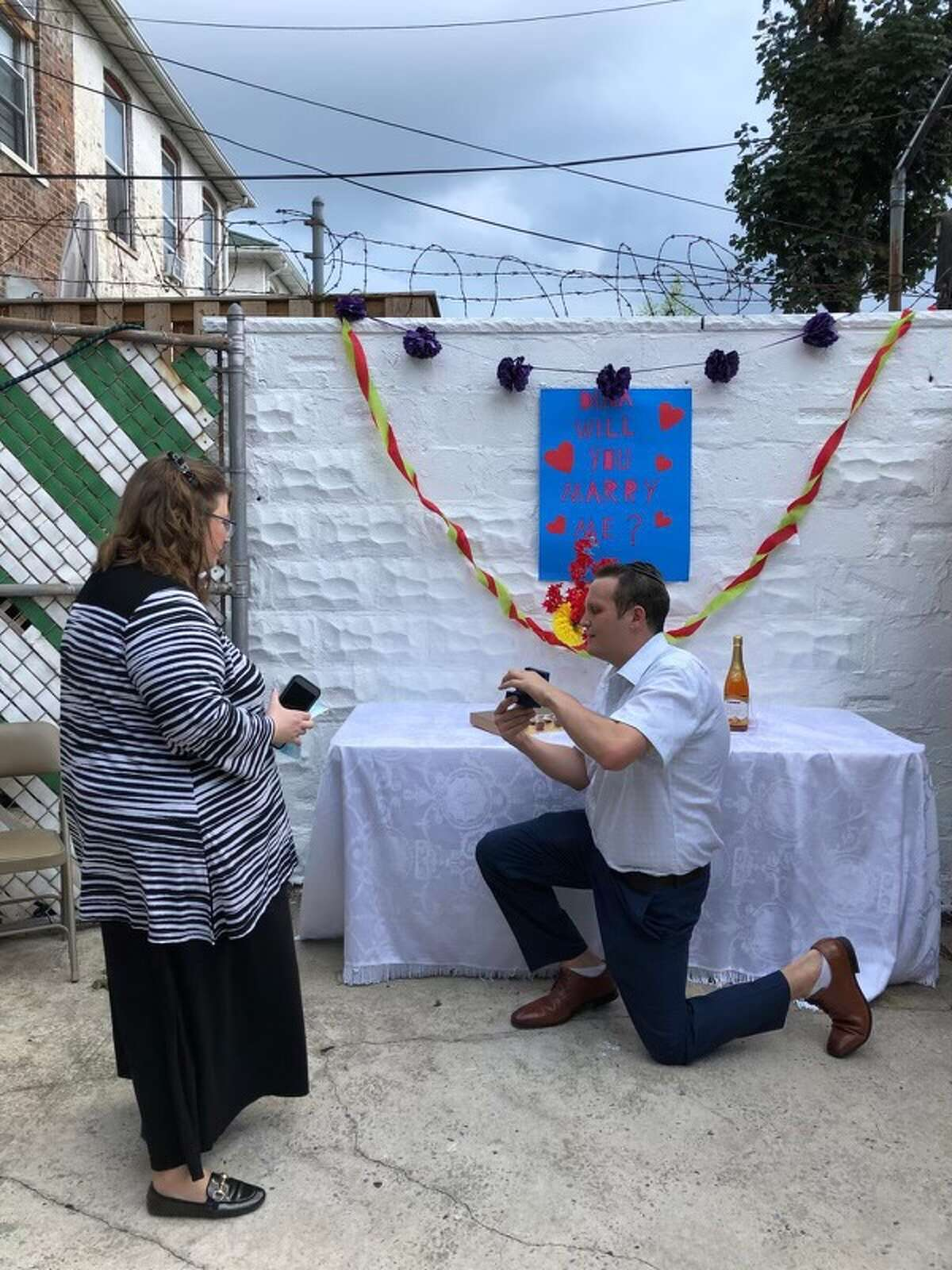 From right, Eli Finkelstein proposes to Dina Wolf in Brooklyn in the summer of 2020. The couple have disabilities and are seeking supportive housing together so they can wed. (Photo courtesy of Ruth Finkelstein)