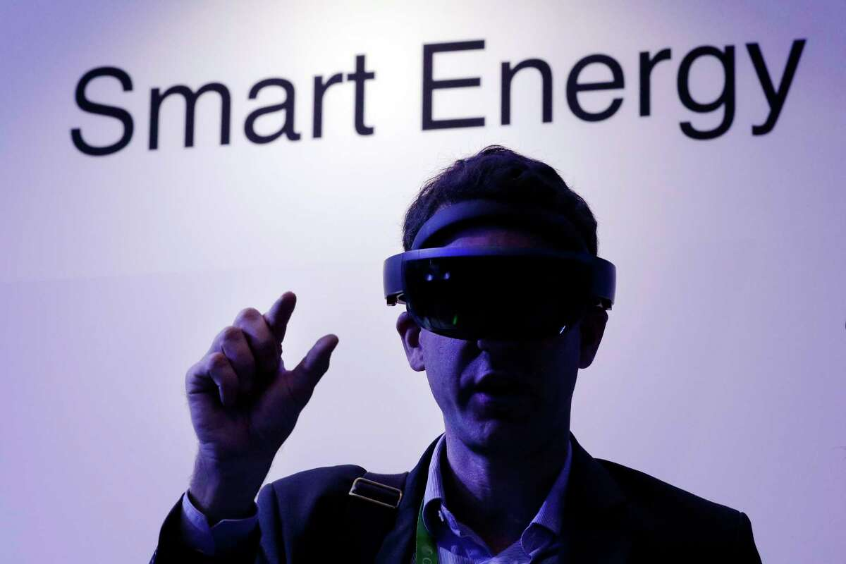 Amid moody and colorful lighting, conference attendant Guillaume de Cumond with Total, tries on an ABB augmented reality headset in the Microsoft room displaying various energy technologies during the second day of CERAWeek by IHS Markit at the George R. Brown Convention Center Tuesday, Mar. 12, 2019 in Houston, TX.