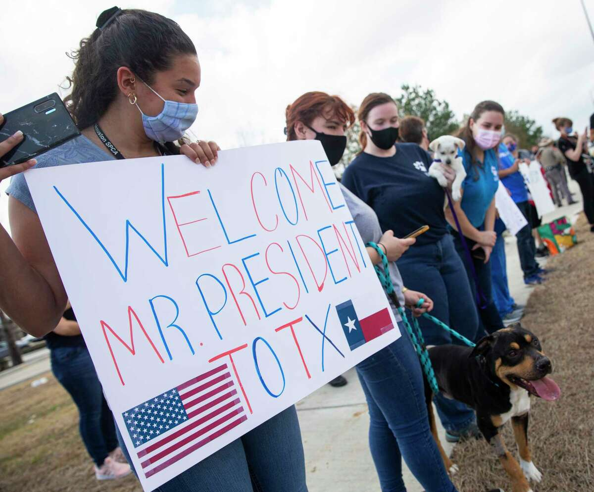 Houston SPCA volunteer and staff bringing out signs and adoptable puppies to welcome President Joe Biden as he is arriving at the Harris County Emergency Operations Center for a tour Friday, Feb. 26, 2021, in Houston.