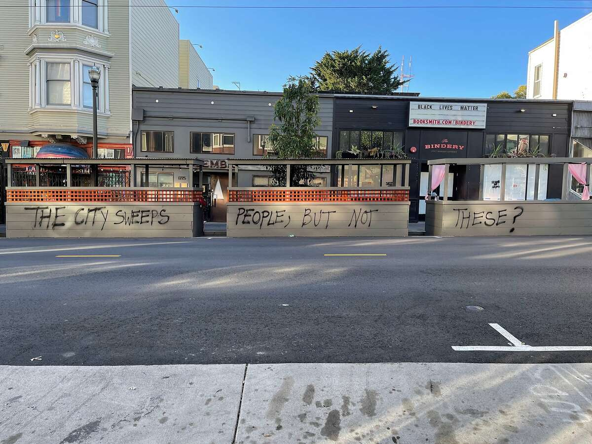 A parklet belonging to Haight-Ashbury bar The Alembic was vandalized with graffiti Thursday. Vandals also installed curtains, a welcome mat and a makeshift dining table.