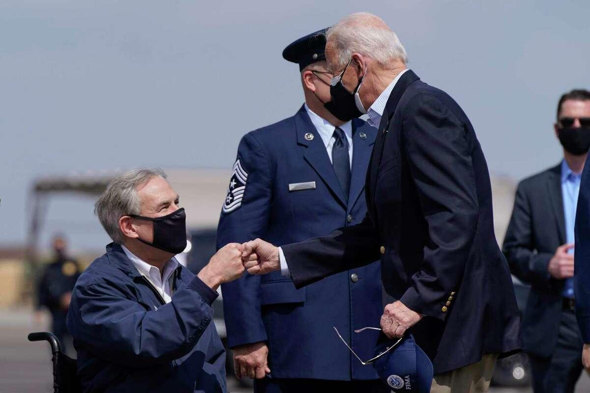 President Joe Biden greets Texas Gov. Greg Abbott after stepping off Air Force One at Ellington Field Joint Reserve Base in Houston, Friday, Feb. 26, 2021. (AP Photo/Patrick Semansky)
