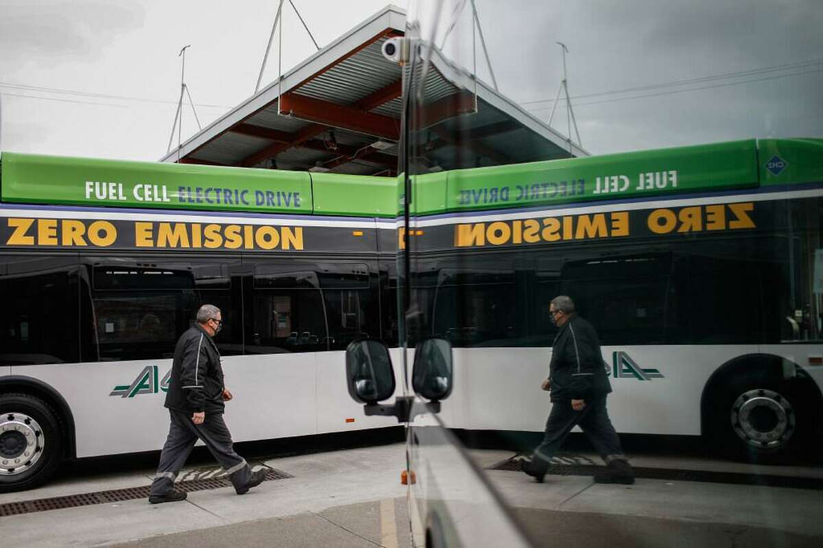 A maintenance worker (declined name) walks past an AC Transit bus that uses hydrogen fuel on Thursday, Feb. 11, 2021 in Emeryville, California. State Sen. Nancy Skinner has proposed a bill that would require the state to designate hydrogen as a priority for its green-energy investments.