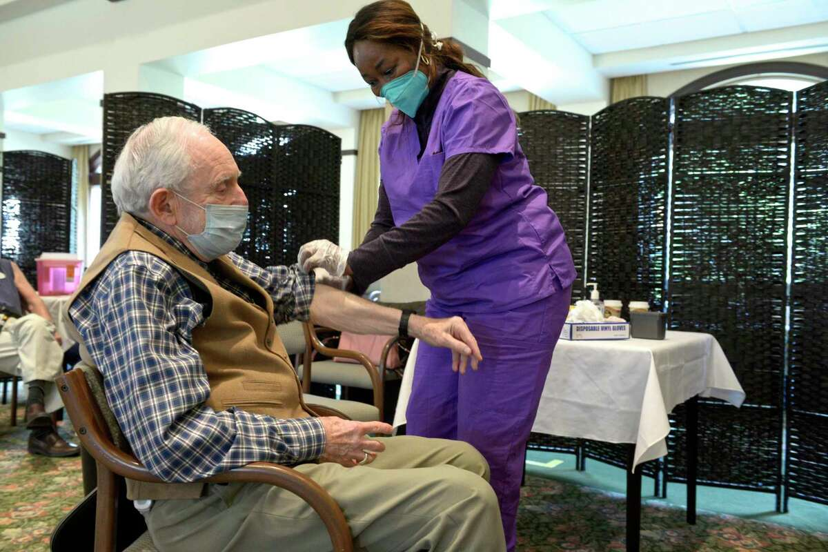 Dr. Arthur Turner, of Meadow Ridge in Redding, receives his COVID-19 vaccination from registered nurse Kerrine McCallum. Danbury-area senior care facilities are divided on requiring the vaccine for employees.