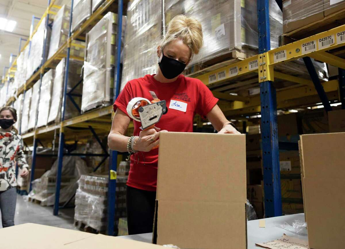 Lisa Akins constructs boxes during a funding acceptance event at the Montgomery County Food Bank, Friday, Feb. 26, 2021, in The Woodlands. Huntsman Corporation were able to raise over $600,000 donated half to two non-profits in Montgomery County.
