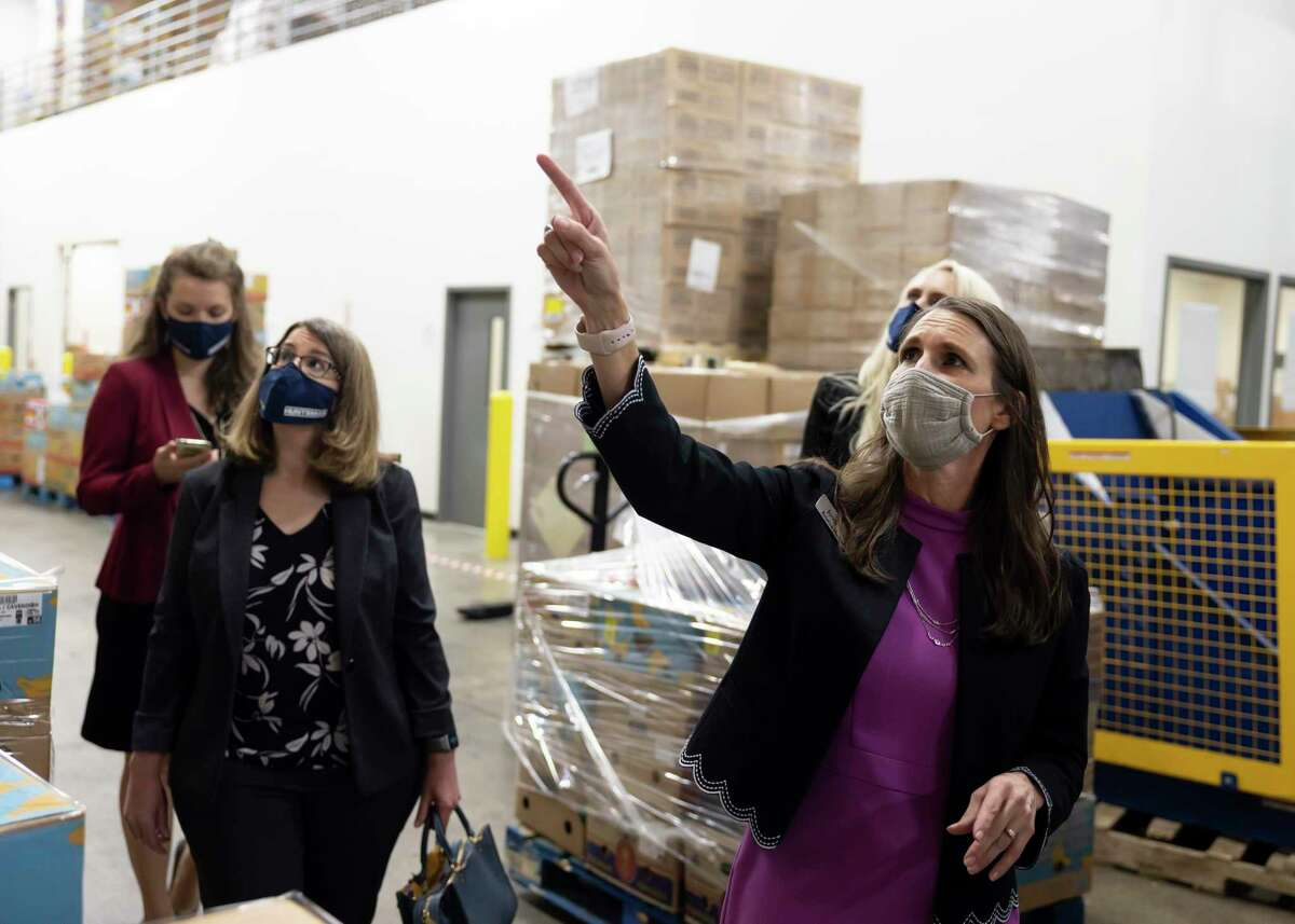 Kristine Marlow, right, CEO and President of the Montgomery County Food Bank, leads a tour for the Huntsman Corporation during a funding acceptance event at the Montgomery County Food Bank, Friday, Feb. 26, 2021, in The Woodlands. Huntsman Corporation were able to raise over $600,000 donated half to two non-profits in Montgomery County.