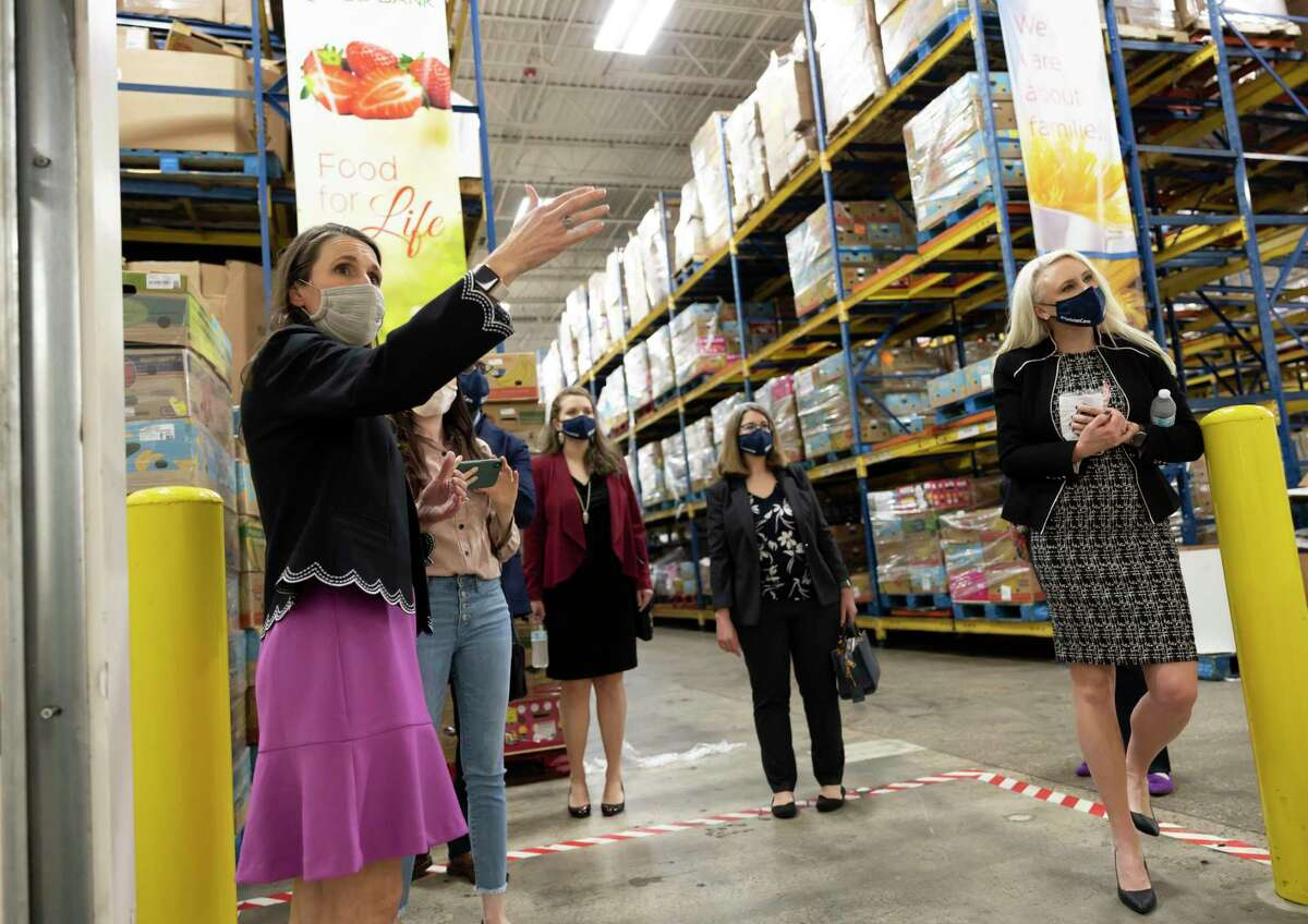 Kristine Marlow, left, CEO and President of the Montgomery County Food Bank, leads a tour for the Huntsman Corporation during a funding acceptance event at the Montgomery County Food Bank, Friday, Feb. 26, 2021, in The Woodlands. Huntsman Corporation were able to raise over $600,000 donated half to two non-profits in Montgomery County.
