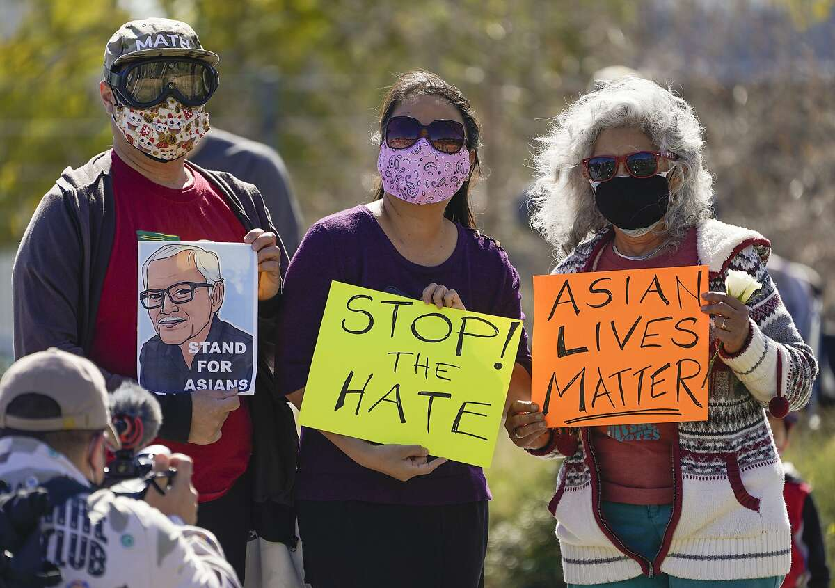 A man holds a portrait of late Vichar Ratanapakdee (left), a 84-year-old immigrant from Thailand, who was violently shoved to the ground in a deadly attack in San Francisco, during a community rally in February.