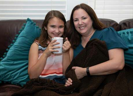 "Annabeth Golden, 12, with mom Heather Golden, finally gets a cup of hot chocolate Friday. Instead of a typically toasty home, the arctic blast left her family in the dark, ""desolate, lonely and cold."""