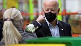 President Joe Biden elbow bumps Joan Hessidence as he tours the Houston Food Bank Friday, Feb. 26, 2021 in Houston.