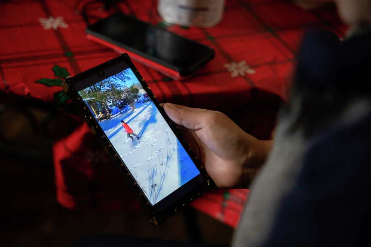 Maria Pineda watches a video of her 11-years-old son play in the snow for the first time in Conroe, Texas. He died of suspected hypothermia on Feb. 16.
