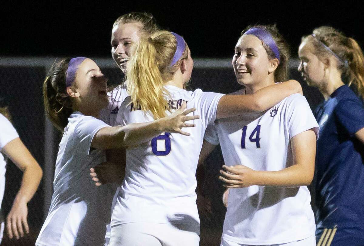 Montgomery midfielder Jenna Attebery (14) is embraced by her teammates after she scores during the first half of a District 20-5A girls soccer game against Lake Creek at Lake Creek High School, Friday, Feb. 26, 2021, in Montgomery.