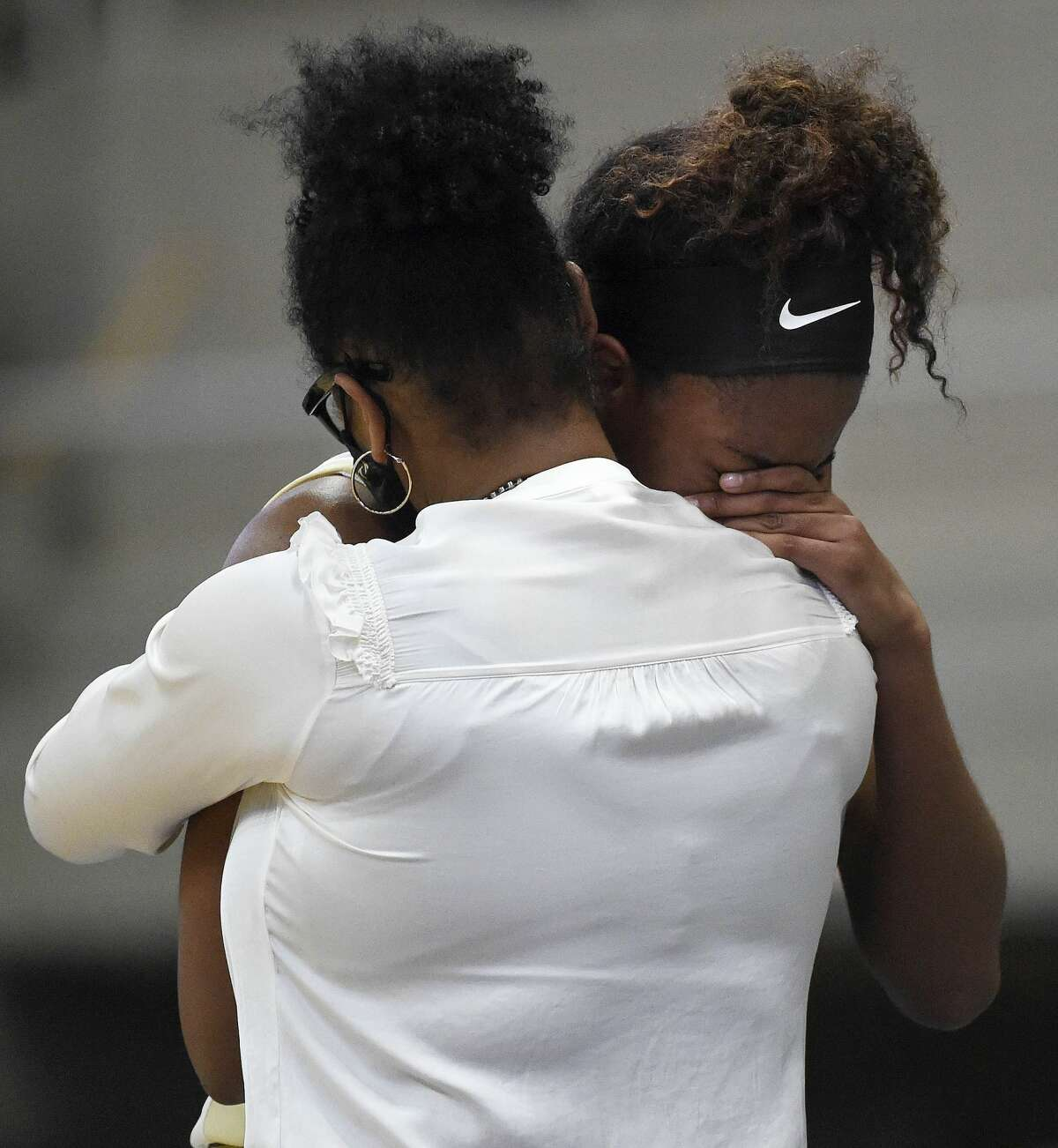 Foster's Kaiya Wynn, right, hugs head coach Savitria Williams-Smith in the final moments of the team's loss to College Station during the second half of a 5A Region III semifinal high school basketball playoff game, Friday, Feb. 26, 2021, in Katy, TX.