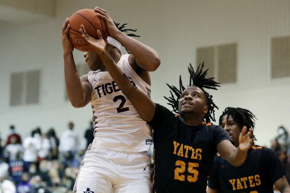 Yates'Joseph Ross (25) reaches in for the rebound as Silsbee's Dre'lon Miller (2) pulls it in during the first half of their 4A-Region 3 playoff basketball game Friday, Feb. 26, 2021 in Dayton, TX.