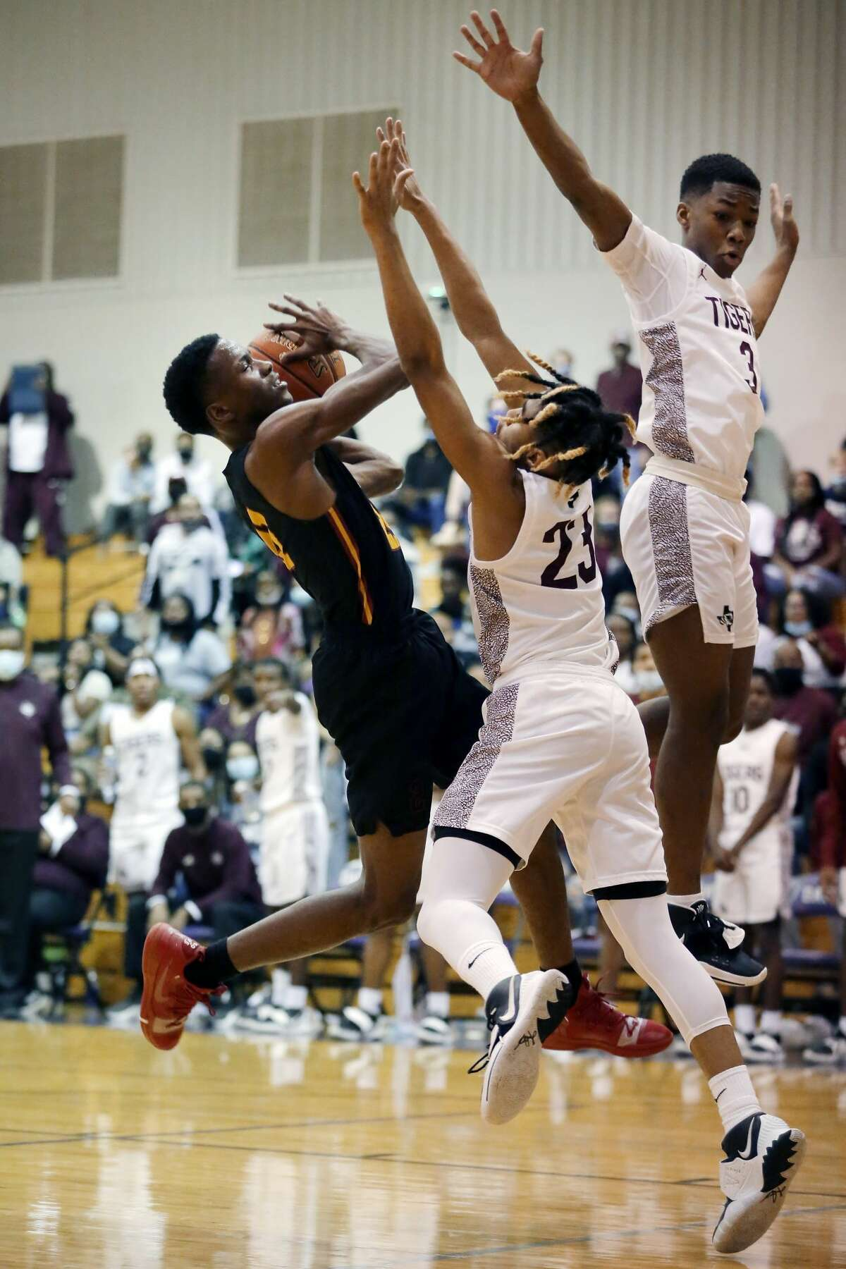Yates'Tyron Bailey, left, drives up a shot against Silsbee's Jerrick Harper (23) and Traivius Haynes (3) during the first half of their 4A-Region 3 playoff basketball game Friday, Feb. 26, 2021 in Dayton, TX.