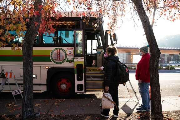 People wait to board a Golden Gate Transit bus heading toward Santa Rosa in Novato, Calif., on Friday, Nov. 20, 2020.