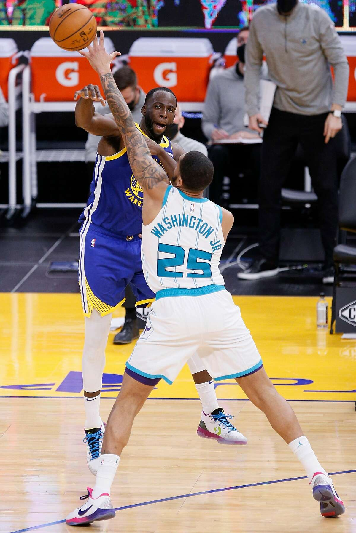 Golden State Warriors forward Draymond Green (23) passes while guarded by Charlotte Hornets forward P.J. Washington (25) in the third quarter of an NBA game at Chase Center, Friday, Feb. 26, 2021, in San Francisco, Calif.
