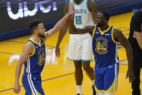 Golden State Warriors guard Stephen Curry, left, celebrates with forward Draymond Green (23) during the first half of an NBA basketball game against the Charlotte Hornets in San Francisco, Friday, Feb. 26, 2021. (AP Photo/Jeff Chiu)