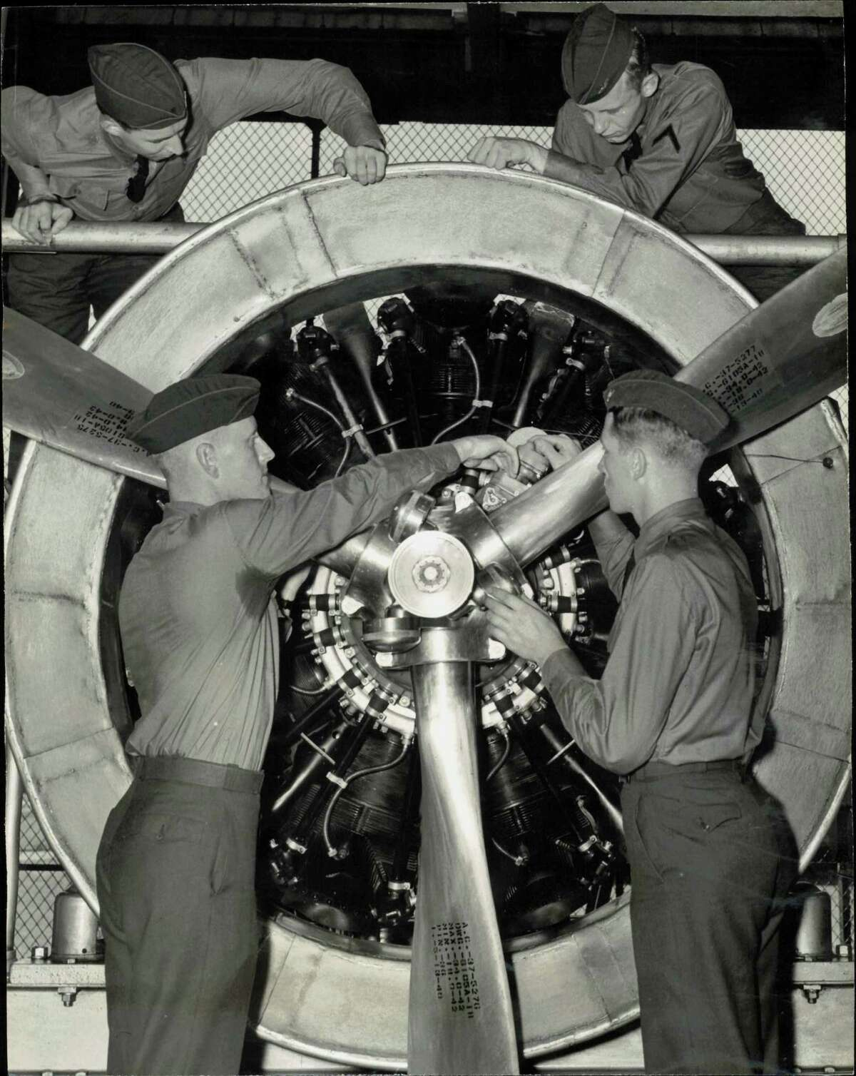 'Trouble-shooting' an air giant - It's a game of hide-and-seek for these flying cadets at Randolph Field, Texas, as they study a huge 900 horsepower plane motor. These cadets are checking a modern two speed supercharger radial engine, the same type used in Uncle Sam's four motored armed bombers.