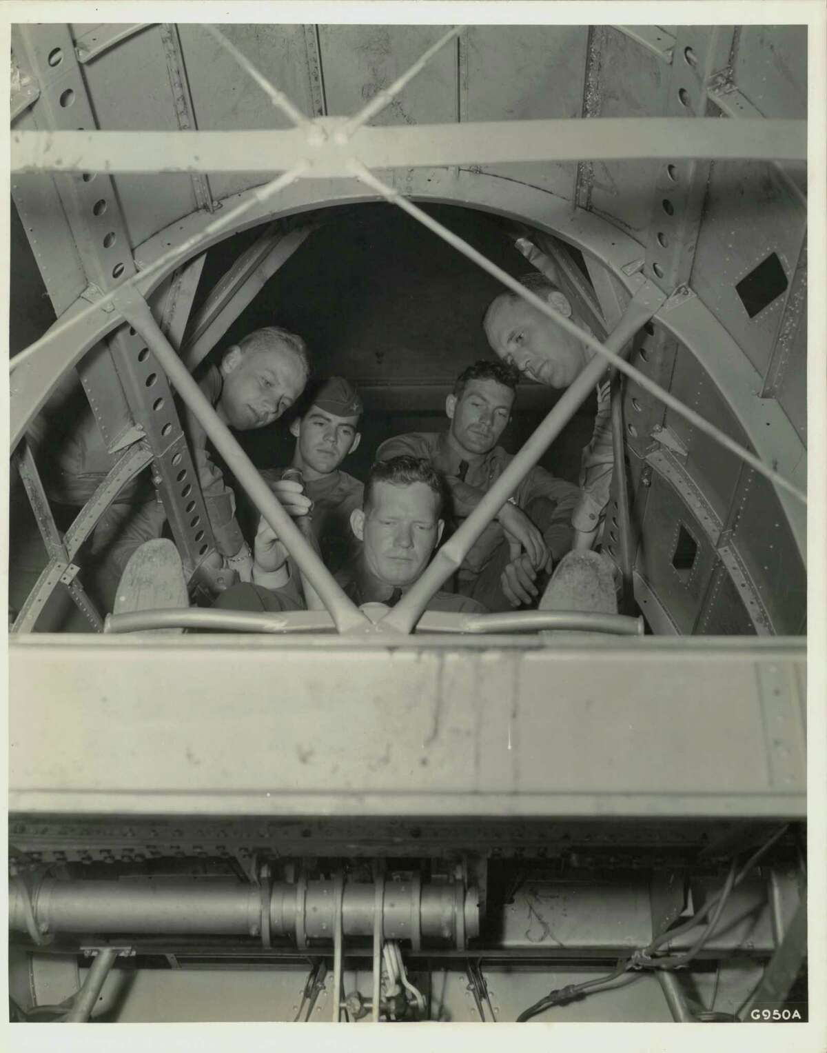 From the bomb bay looking up -- Inside a full scale cutaway model of a giant twin motored plane, used at Randolph Field, Texas, for ground instruction, a group of Flying Cadets experiment with the controls. Uncle Sam is going to train 7,000 pilots annually for his Air Corps and 3,600 bombardiers and navigators. A good idea of the intricate construction of a modern fighting plane can be obtained here. (Texas)