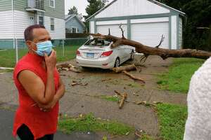 Andrea Ollivierre inspects damage to her vehicle after a tree fell onto it during tropical storm Isaias on Thomas Street in West Haven, Conn., on Tuesday Aug. 4, 2020.