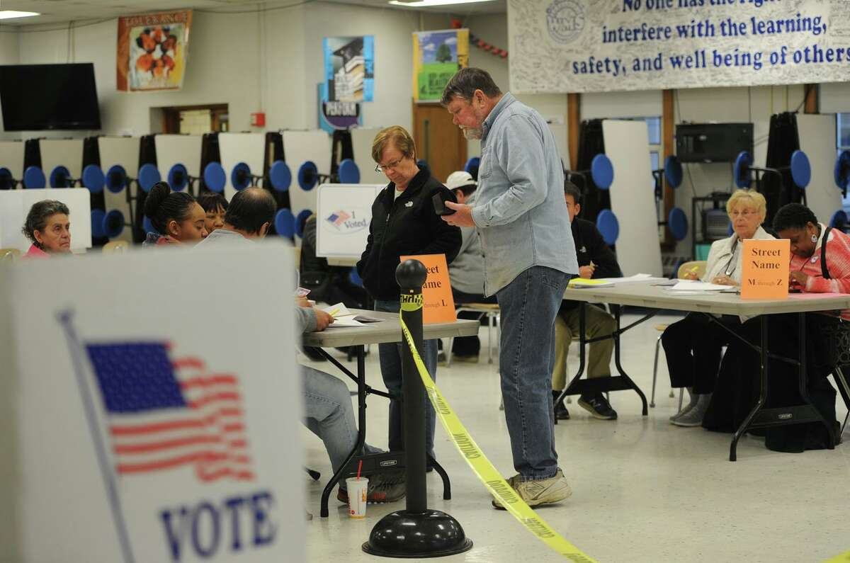 A file photo showing voters checking in to pick up their ballots at Wooster Middle School in Stratford, Conn. on Tuesday, November 7, 2017. The polling place saw a strong turnout all day according to an election official on site.