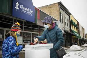 Elise LeBlanc, 9, left, and Emily Lyons, right, play a game of checkers on a board made of ice during the Winter Fest Saturday, Feb. 27, 2021 in downtown Midland. Visitors enjoyed ice games, outdoor dining and live music during the event. (Katy Kildee/kkildee@mdn.net)