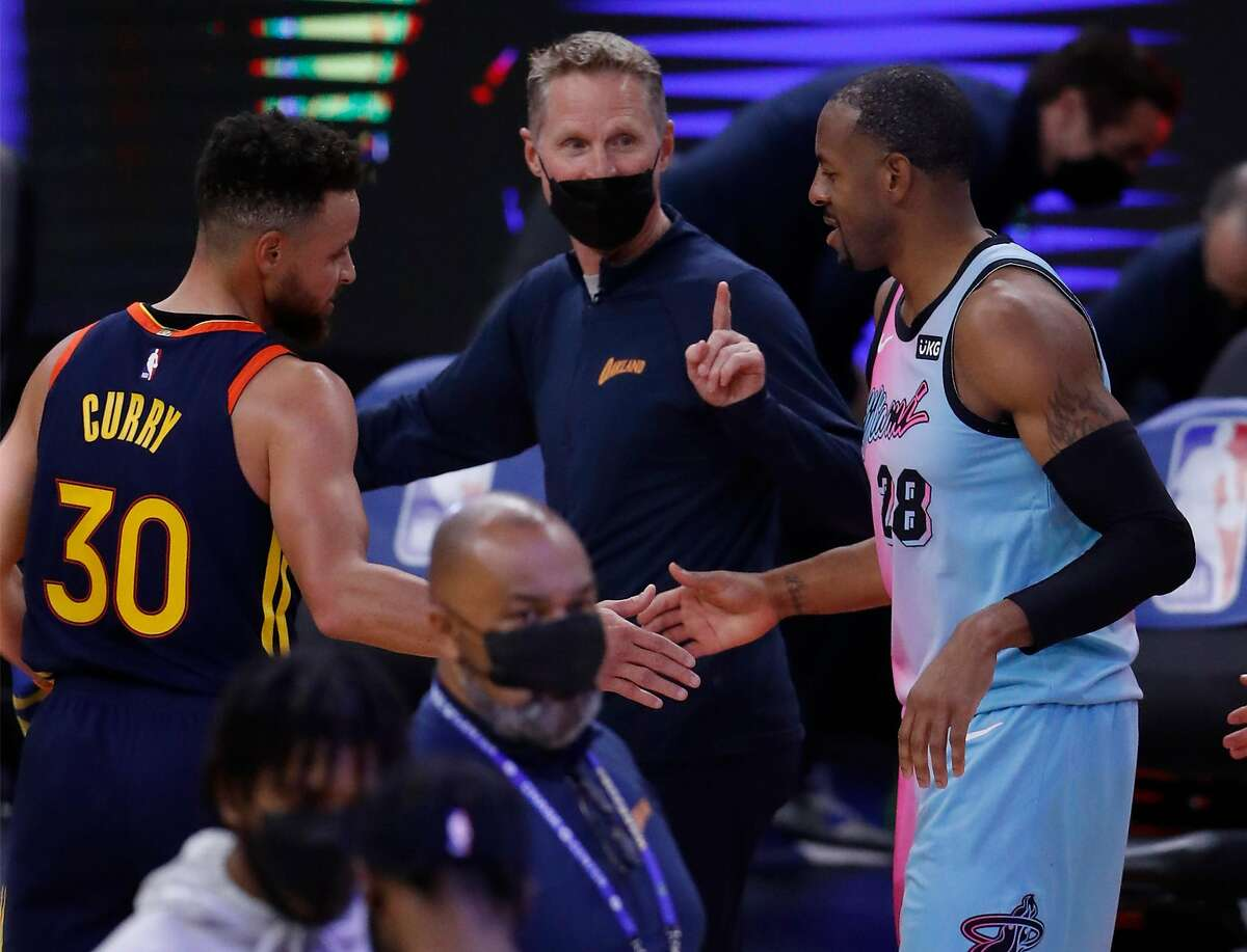 Golden State Warriors' head coach Steve Kerr, center, and Stephen Curry greet former Warrior - and current member of the Miami Heat - Andre Iguodala after the Warriors' 120-112 overtime win at Chase Center on Feb. 17.