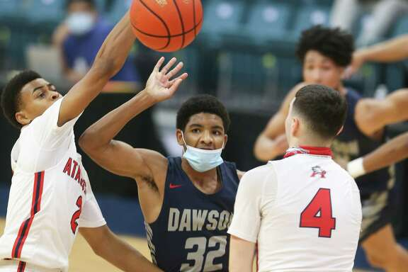 Atascocita's Angel Johnson (2) goes after a loose ball against Dawson's Jaylen Carhan (32) at Merrell Center in Katy on Saturday, Feb. 27, 2021. Atascocita won the game 55-54.