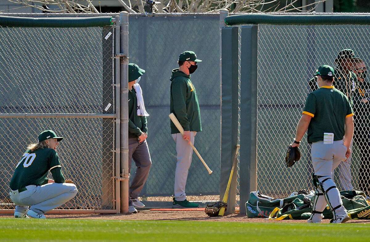 Manager Bob Melvin watches A's pitchers work in the bullpen during Saturday's spring training practice in Mesa, Ariz.