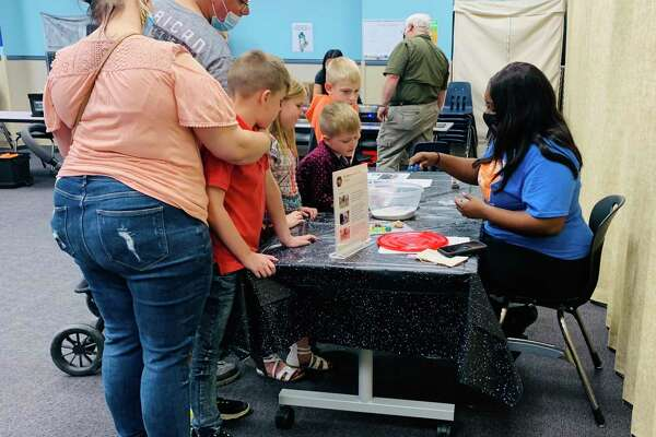 "A family learns how craters are created on the moon during the Beaumont Children's Museum's ""Race to the Moon Day"" on Saturday, Feb. 27."