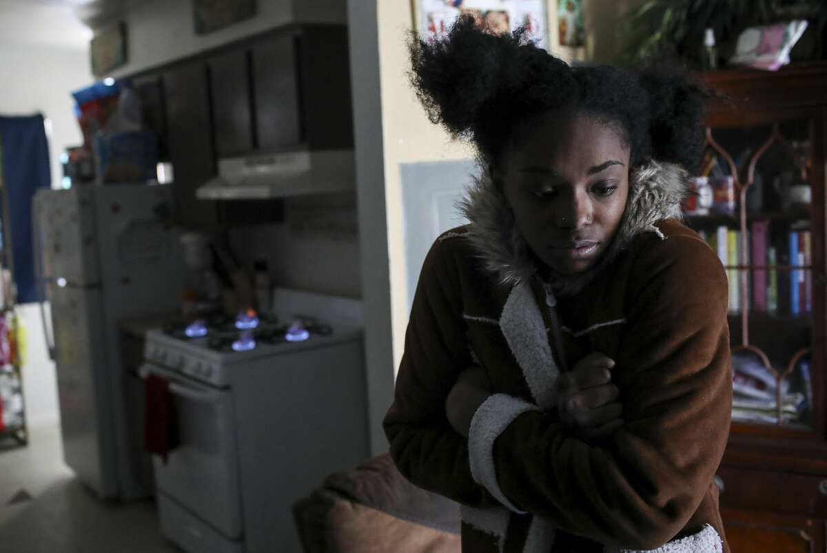 Shanice Ardion tries to warm up with a gas stove at Cuney Homes on Feb. 16. She said the stove was their only source of heat since the power went out the day before.