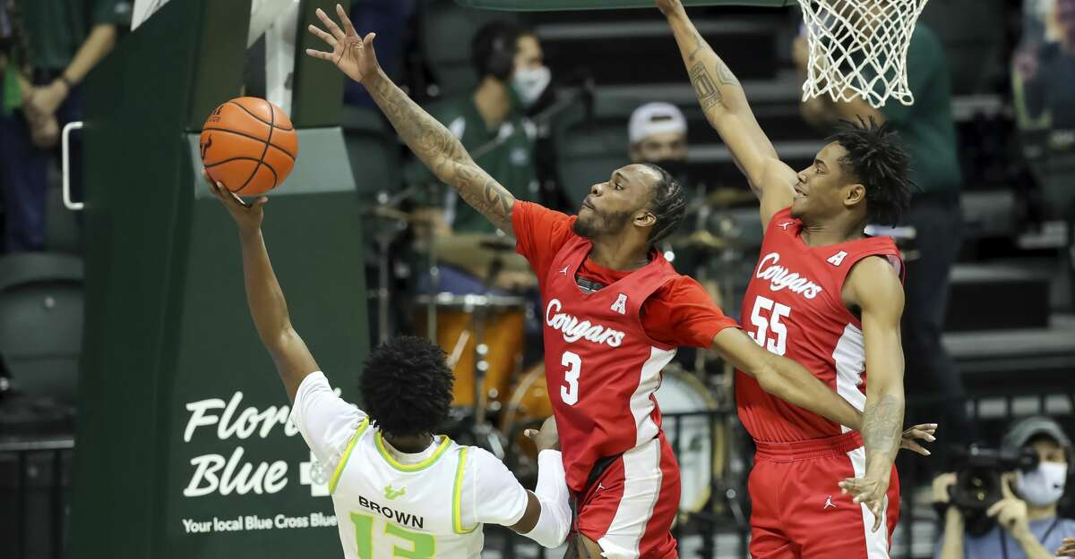South Florida's Justin Brown (13) has his shot defended by Houston's DeJon Jarreau (3) and Brison Gresham during the first half of an NCAA college basketball game Wednesday, Feb. 10, 2021, in Tampa, Fla. (AP Photo/Mike Carlson)