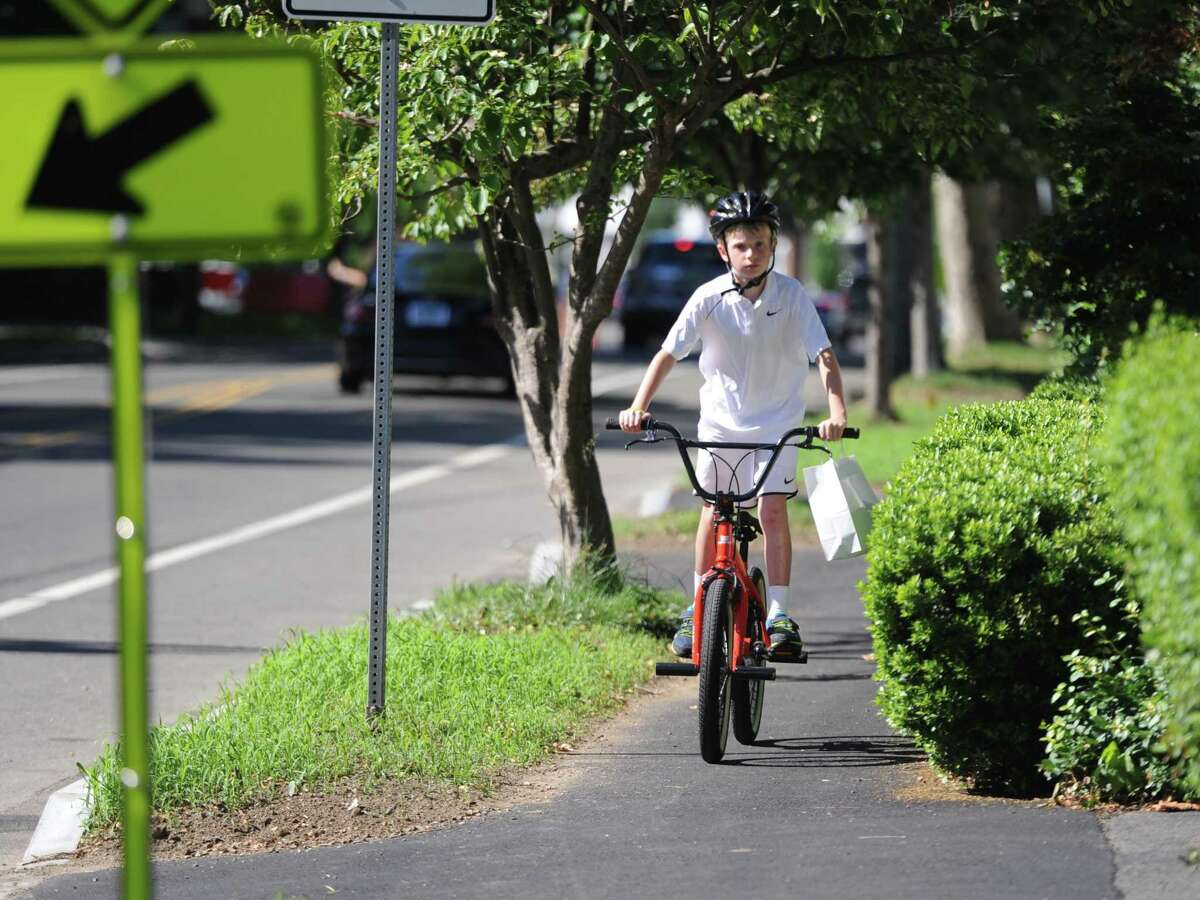 A boy rides his bike on the sidewalk in Old Greenwich, Conn. Monday, June 25, 2018. Efforts to have more bicycle friendly policies in Greenwich are ramping up and an event from Pedal Greenwich will be held in Old Greenwich on Saturday.