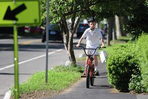 A boy rides his bike on the sidewalk in Old Greenwich in 2018. The route study would look to find the best east-west route for bicyclists across town but it needs BET approval even with private money commitments to fund half of the study.